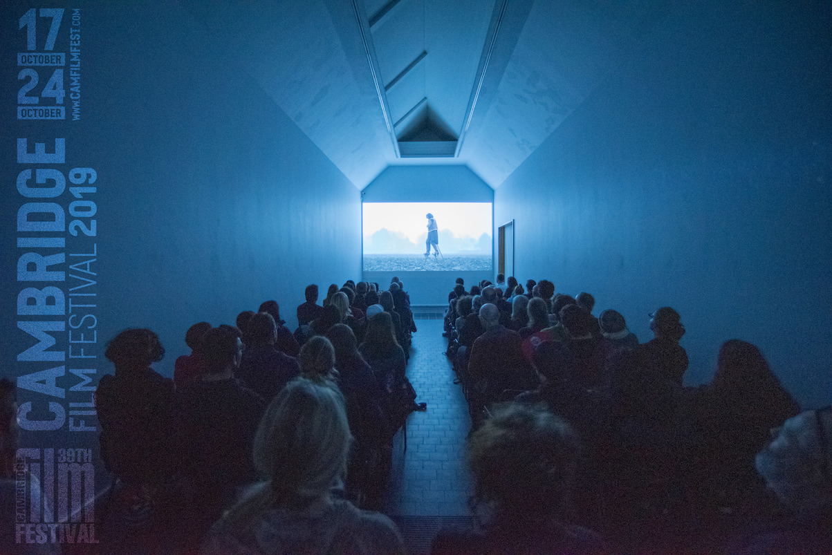 An audience illuminated by a blue screen