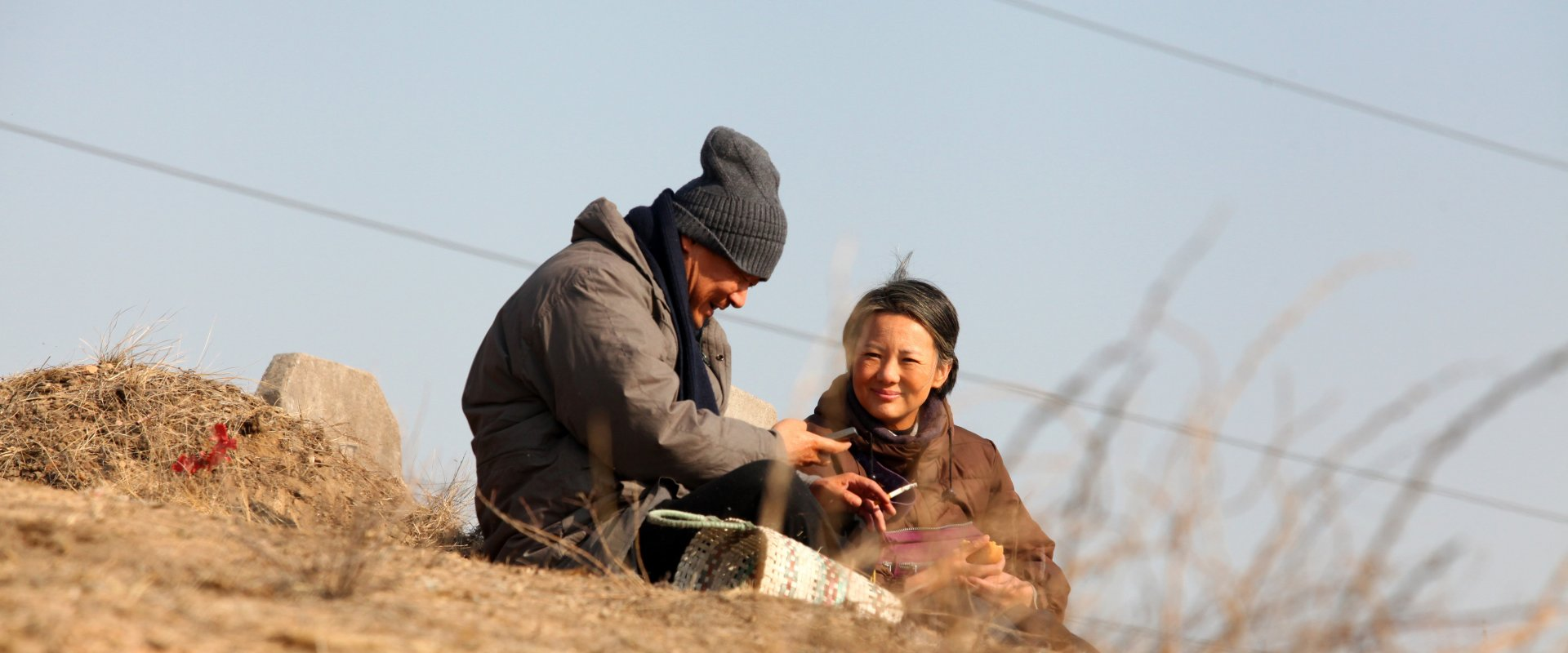 A man and a woman sit on a barren hillside, looking happily