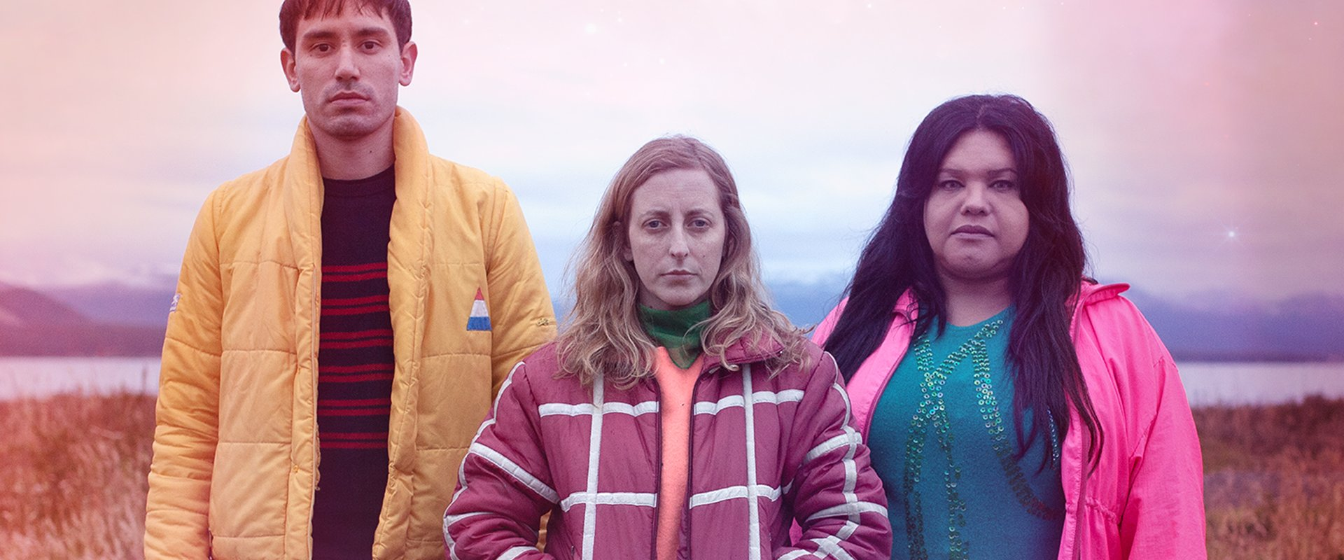 Three people standing in a field in an eerie pink light