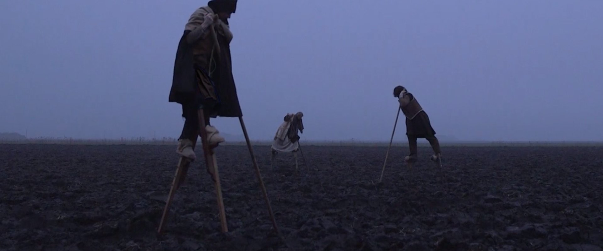 Three people on stilts are moving in a barren foggy landscape