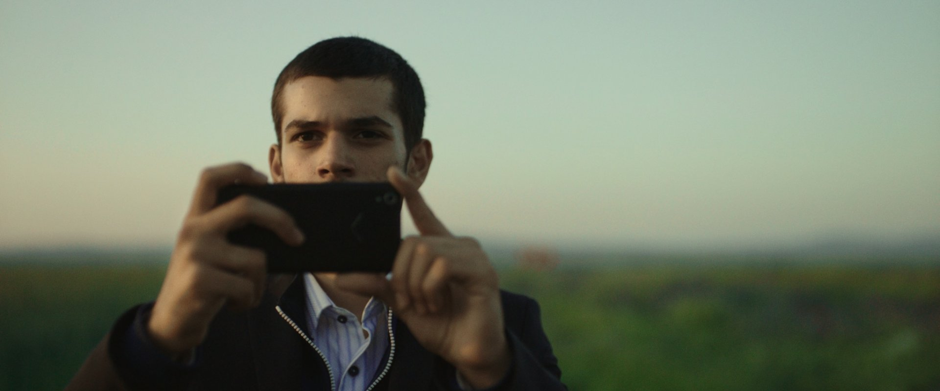 Man with phone-camera close up with exterior landscape in background