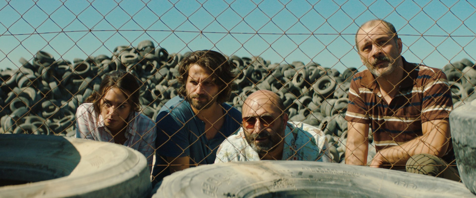 three men and a woman looking through a chain-link fence