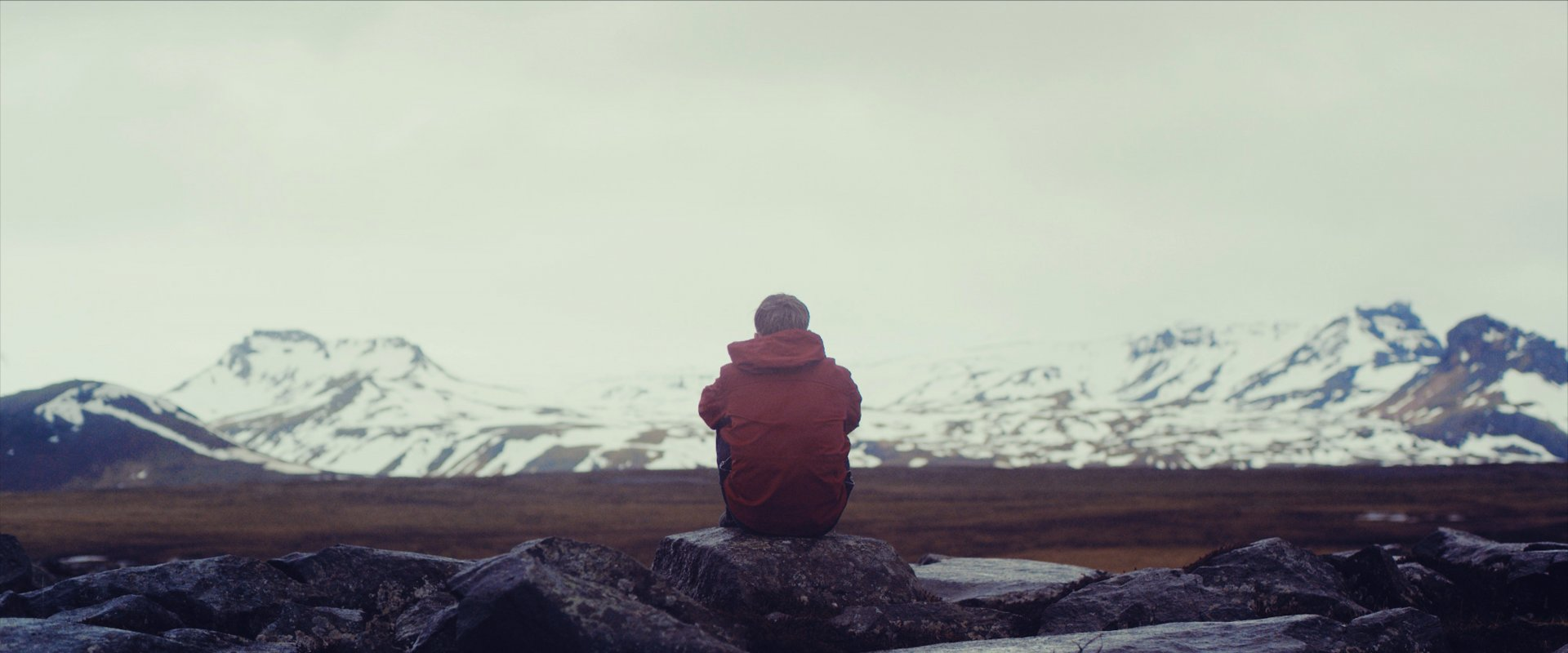 man sitting on a rock in front of wide frozen open views