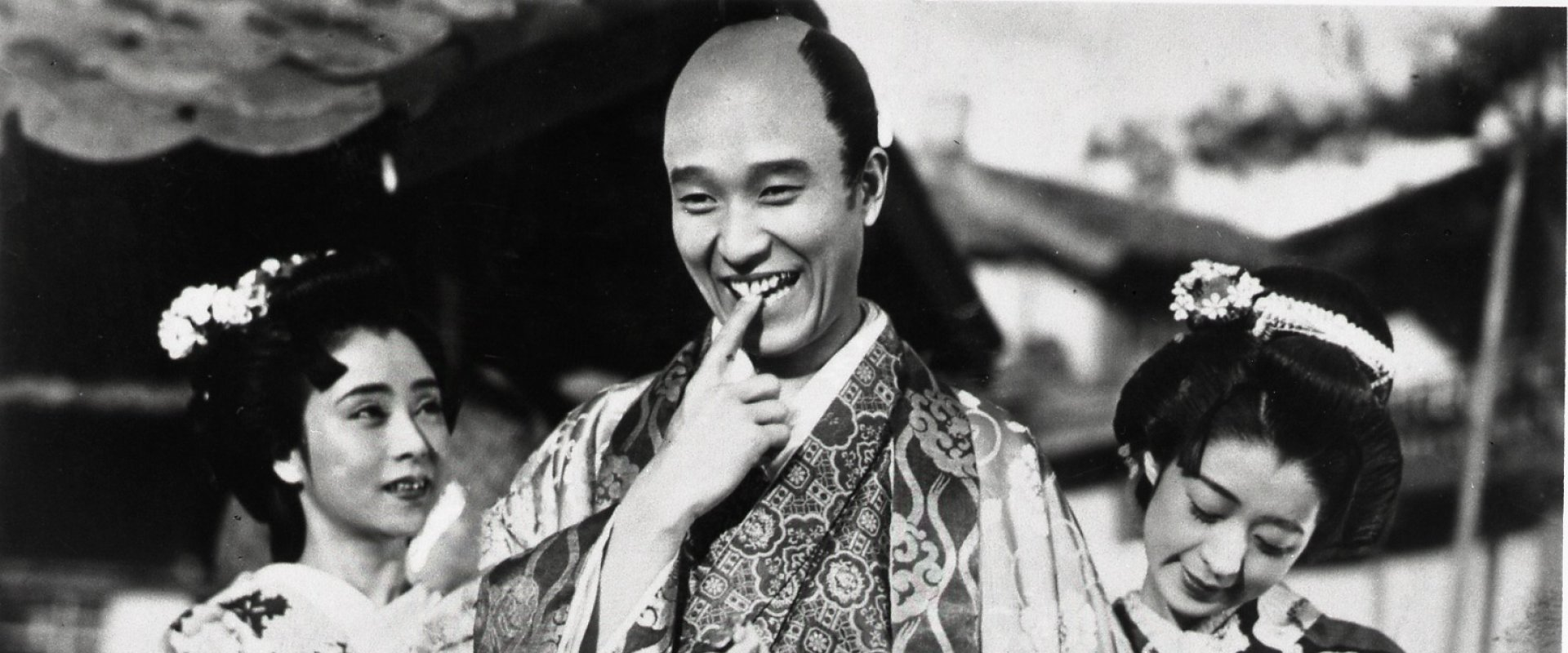 Man in traditional Japanese dress bites his finger in a bashful gesture.