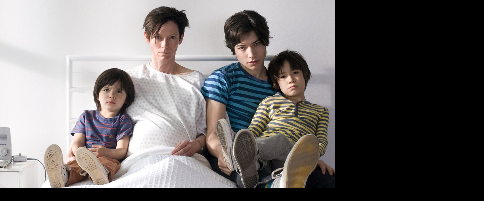 pregnant mother sitting on hospital bed with the 3 actors who play Kevin at different stages in his life