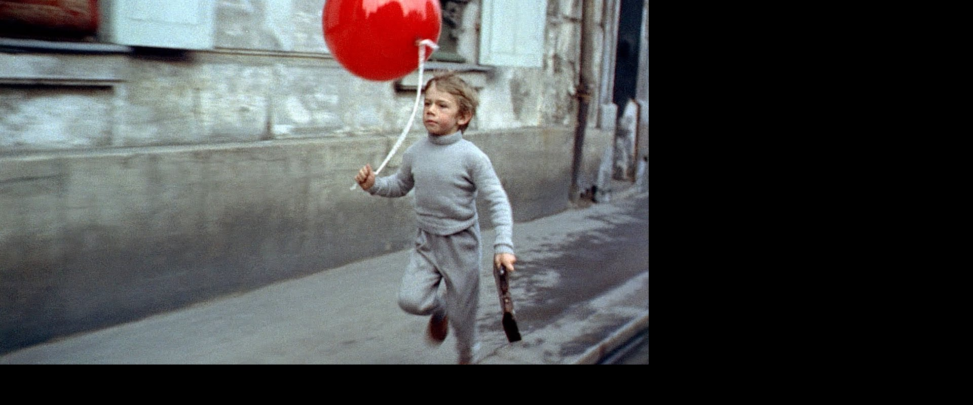 a boy, holding a red balloon is running down a street