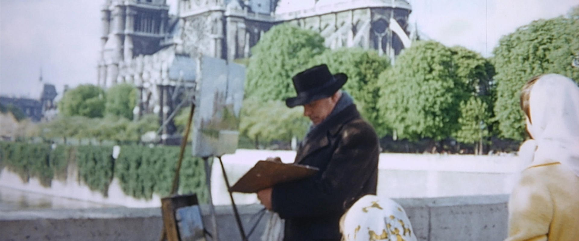 man painting in the street with women in head scarves