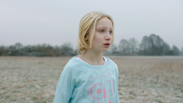 A young girl stands in an empty field looking worried