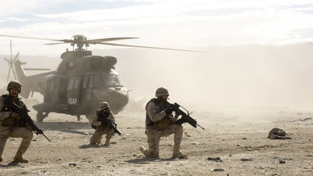 a soldier is kneeling down holding a gun with a helicopter in the background
