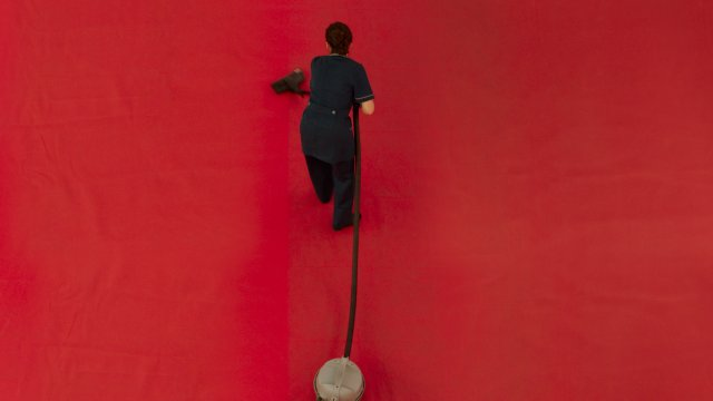 A nurse vacuums a red carpet. Aerial shot
