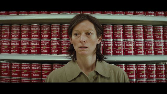 Mom looking lost in supermarket in front of red cans