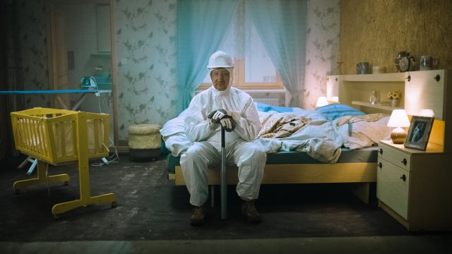 man sitting on bed in white overalls