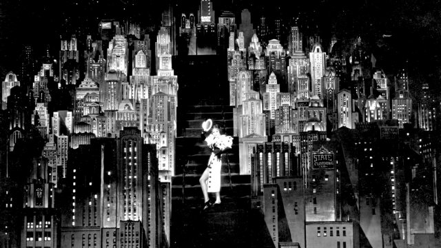Female dancer walks down the stairs in front of a dramatic backdrop of a city.