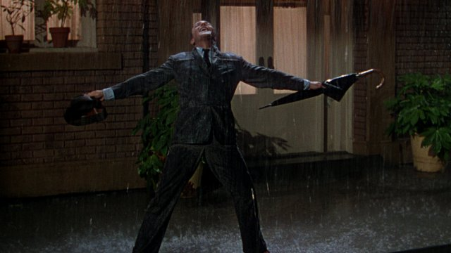 Gene Kelly raises his arms to enjoy the rain as he dances down the street.
