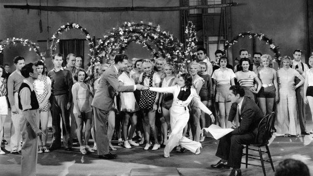 A man leads a woman into a dance in front of the cast and crew