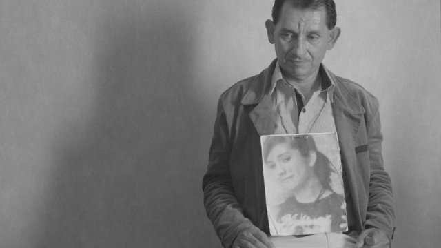 A man holding an image of a woman