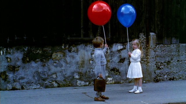 a boy with a red balloon and a girl with a blue balloon are standing opposite each other on the street
