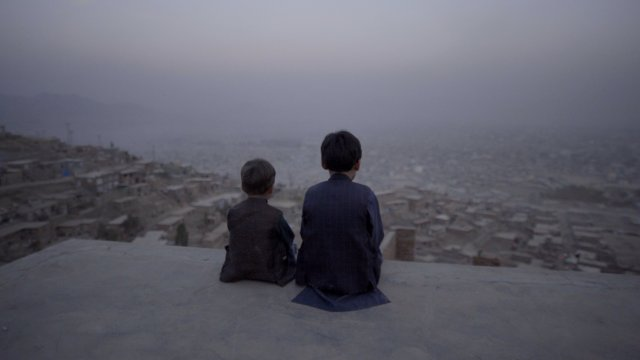 Two boys sit on a rooftop overlooking a city landscape