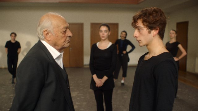 An older man stands opposite an intimidated-looking young man in a dance studio