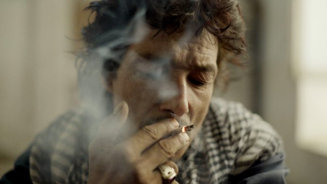 grizzled man smoking roll-up cigarette
