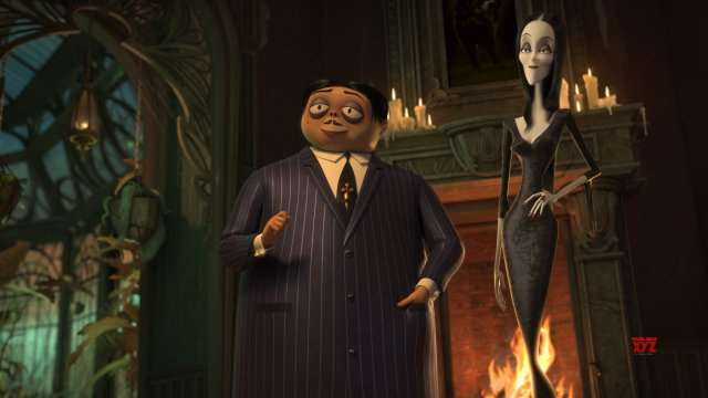 Gomez and Morticia stand in front of a fireplace