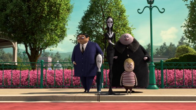 The Addams Family stand together on the ride of a road on a sunny day