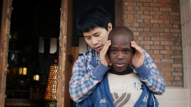An asian man holds the head of a black man