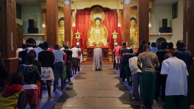 A procession of people stands in a temple facing a gold buddha