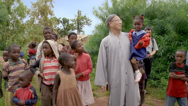 An asian man stands surrounded by a group of children