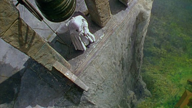 A nun stands at the edge of church with a sheer drop