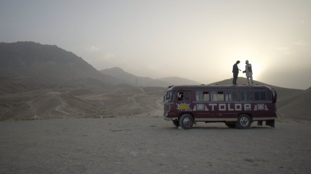 two men standing on a bus in the desert