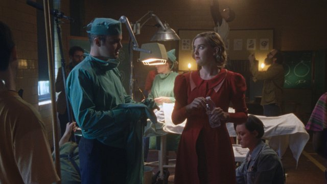 A Woman in Red stands in an Operating Theatre full of Doctors and Nurses.