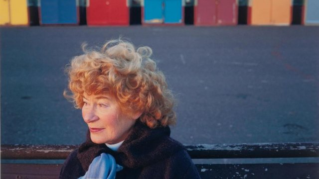 Shirley Collins in front of beach huts