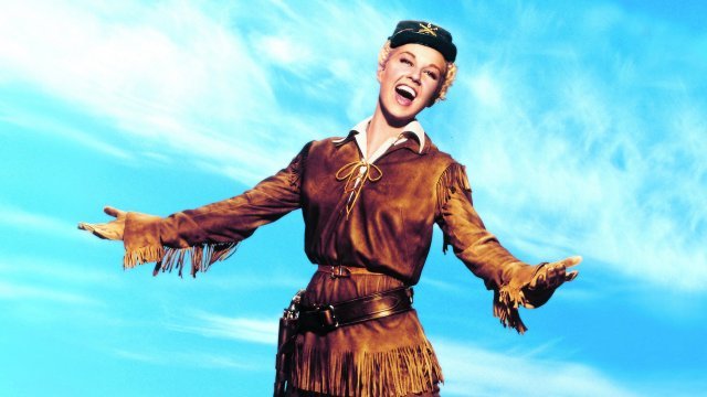 Doris Day dressed as a cowboy sings triumphantly.