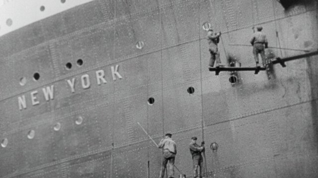 Side of a large boat with workmen working on it.