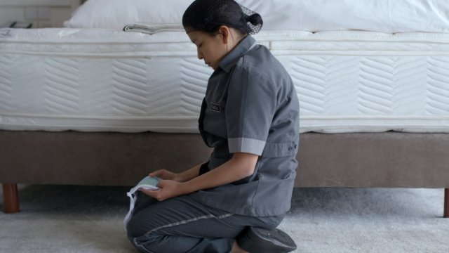 A woman in a cleaners uniform kneel in front of an unmade bed.