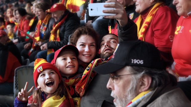 A woman takes a selfie with 3 children in the crowd of the football game