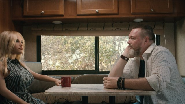 A man sits in a trailer looking at a rubber, robot woman