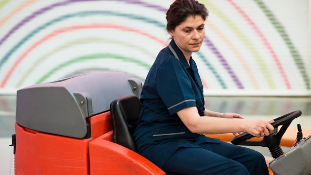 A nurse drives a large floor cleaning machine