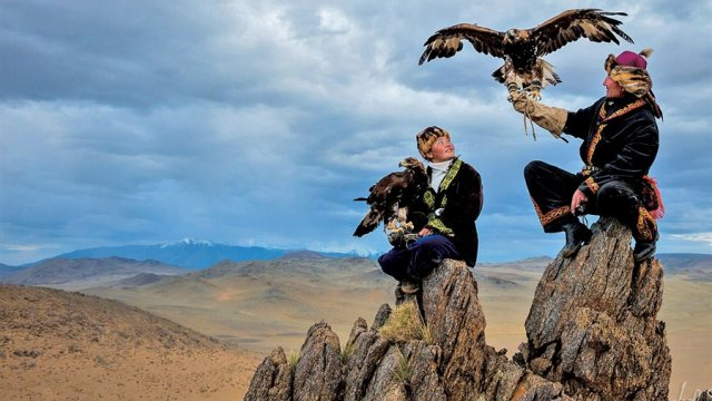 two people are sitting on rocks, holding eagles