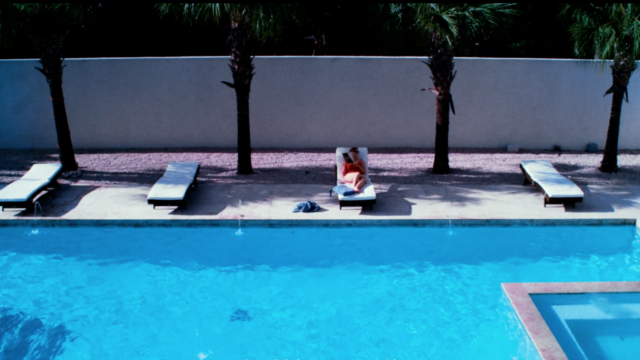 woman lying next to a pool on a sunchair