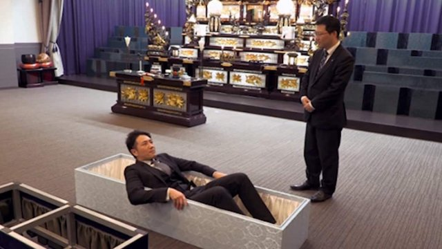 A business man looks uncomfortable as he tries out a coffin in a funeral showroom.