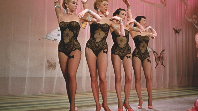 Four showgirls pose during a dance on stage