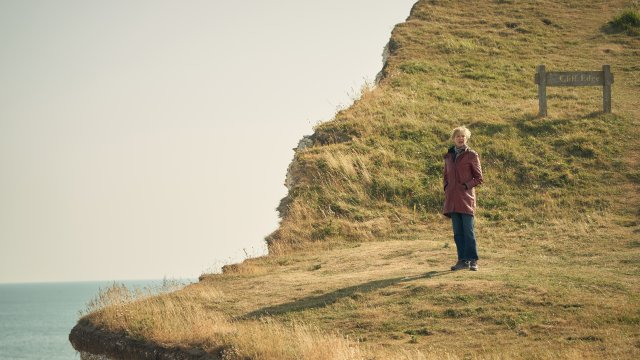 Annette Bening stands at a grassy cliff edge, gazing into the distance