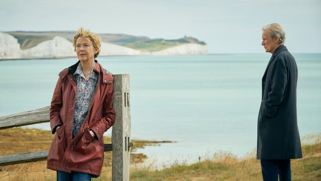 Against a seaside backdrop, Annette Bening and Bill Nighy stand with a distance between them. Bening faces the opposite direction while Nighy gazes at the floor