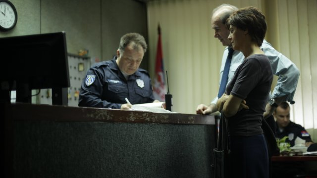 man and woman in policestation, with policeman filling out a form