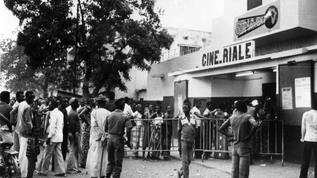 A crowd of people stand outside a cinema