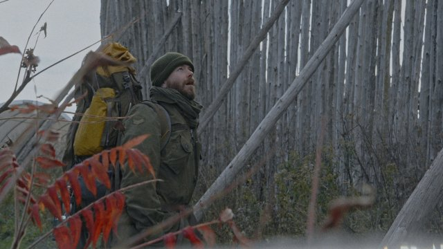Hiker man looks up at a tall wooden fence in front of men, in awe