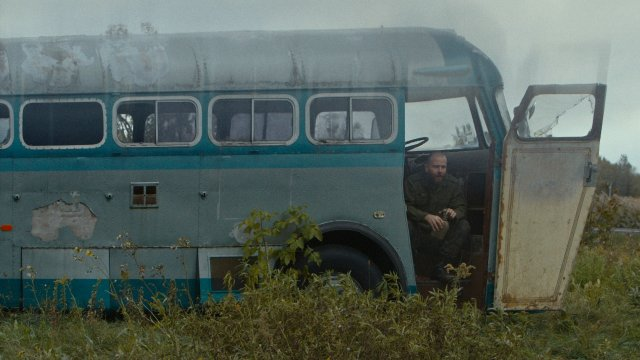 Man sits at the door entrance of a run-down abandoned bus
