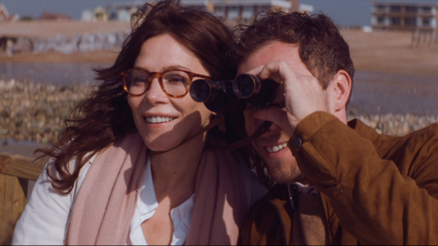 woman and man on bench at beach with binoculars